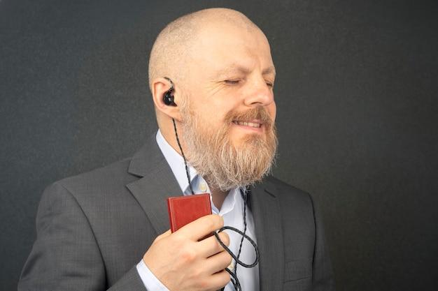 Bebaarde zakenman luistert graag naar zijn favoriete muziek via een audiospeler in een kleine koptelefoon. audiofiel en muziekliefhebber. muziek en hifi-geluid