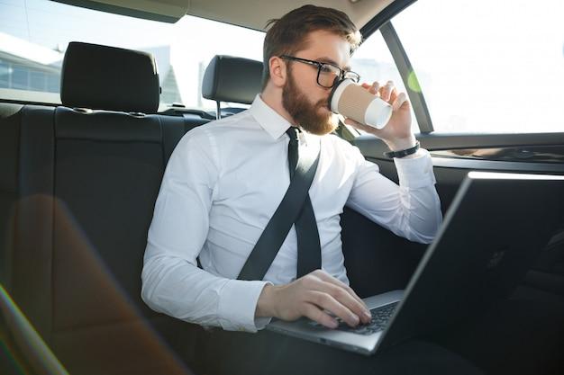 Bebaarde zakenman met behulp van laptop en koffie drinken