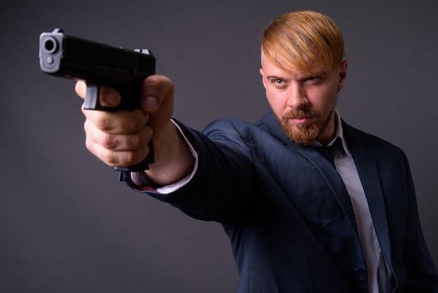 Bebaarde zakenman met pistool op grijs