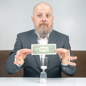 Bebaarde zakenman ontvangt een kleine vergoeding voor werk met geld tegen de achtergrond van een zandloper.