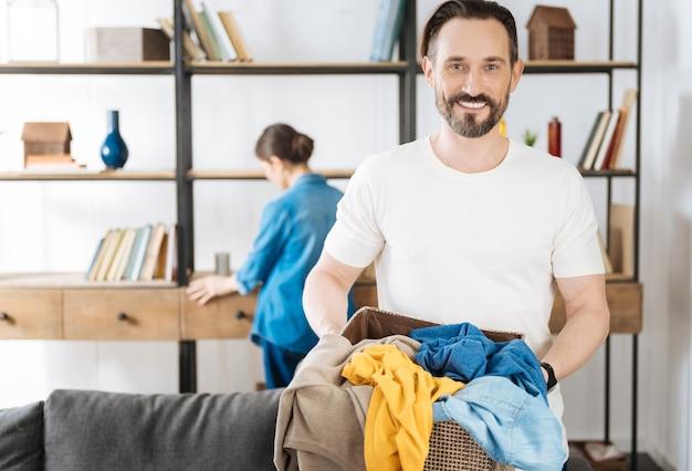 Bebaarde zelfverzekerde vrolijke echtgenoot die zich voordeed op de onscherpe achtergrond tijdens het glimlachen en het dragen van mand