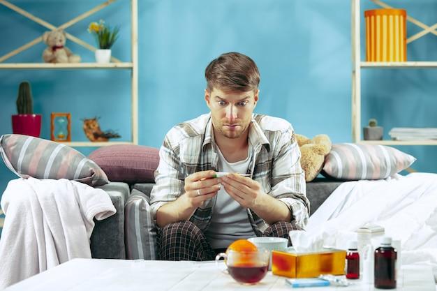 Bebaarde zieke man met rookkanaal zittend op de bank thuis en het meten van de lichaamstemperatuur. het concept van de winter, ziekte, griep, pijn. ontspanning thuis