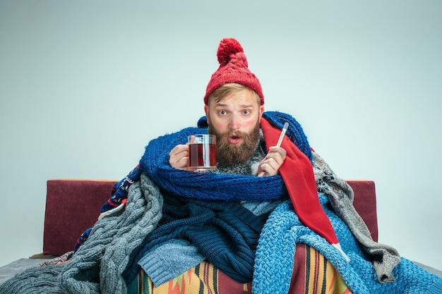 Bebaarde zieke man met rookkanaal zittend op de bank thuis of studio met kopje thee bedekt met warme gebreide kleding. ziekte, influenza-concept. ontspanning thuis. gezondheidszorgconcepten.