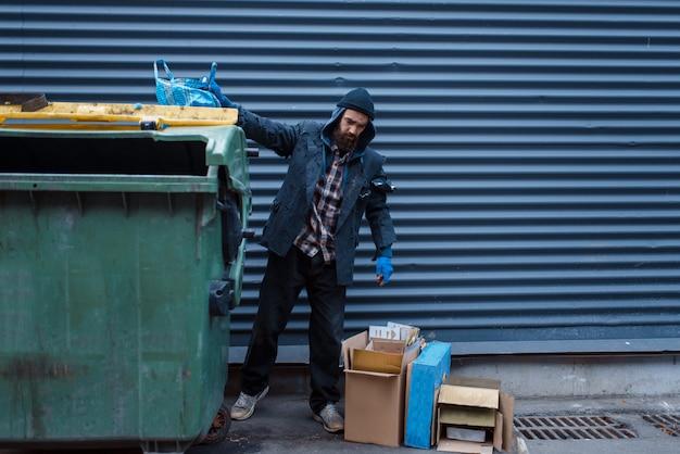 Bebaarde zwerver die voedsel in vuilnisbak op straat zoekt
