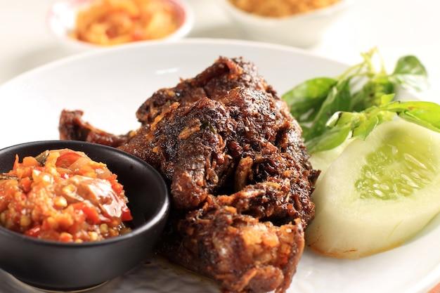 Bebek madura, traditioneel gebakken eendmenu in het indonesisch. populair menu kwam uit madura, oost-java. meestal geserveerd met rauwe groente en pittige sambal. populair als penyetan