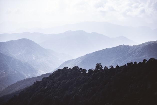 Beboste bergen in een god onder een bewolkte hemel