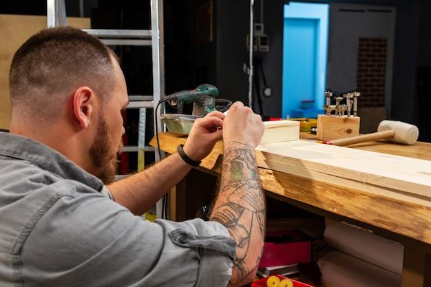 Bebouwd beeld van de handen van een bekwame vakman die een houten plank met een cirkelzaag in een workshop snijden