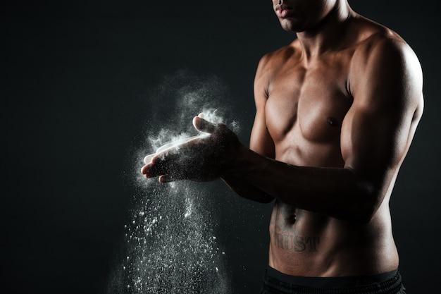 Bebouwd beeld van de knappe mens die van afro amerikaanse sporten handen met krijt wrijven