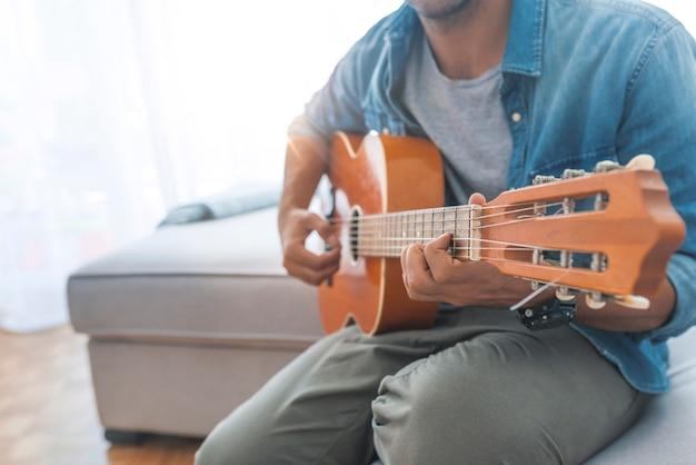 Bebouwd beeld van de knappe mens in vrijetijdskleding die gitaar thuis spelen