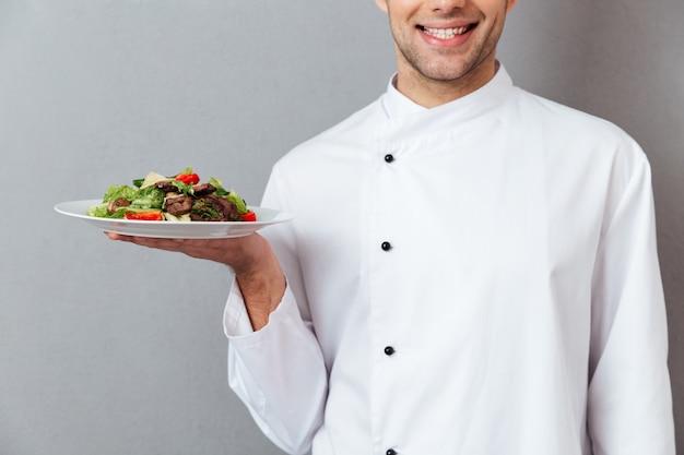Bebouwd beeld van een glimlachende mannelijke chef-kok gekleed in eenvormig