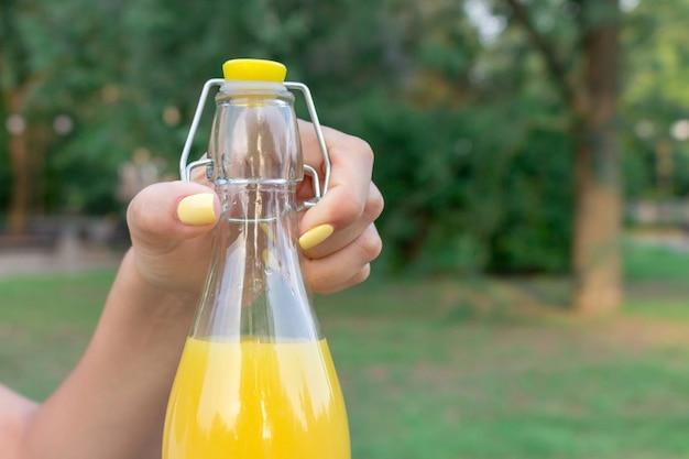 Bebouwd beeld van een vrouw terwijl het openen van een koude fles limonade in een hete dag in het park