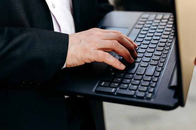 Bebouwd beeld van hogere laptop van de zakenmanholding in zijn hand en het typen close-up.