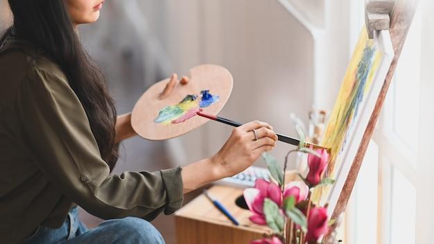 Bebouwd beeld van jong kunstenaarsmeisje die een verfborstel houden en olieverf trekken op canvas