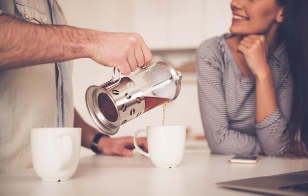 Bebouwd beeld van knappe mensen gietende thee