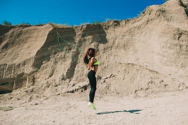 Bebouwd beeld van sportenmeisje in zweetbroek en tennisschoenen die touwtjespringen in de ochtendzon