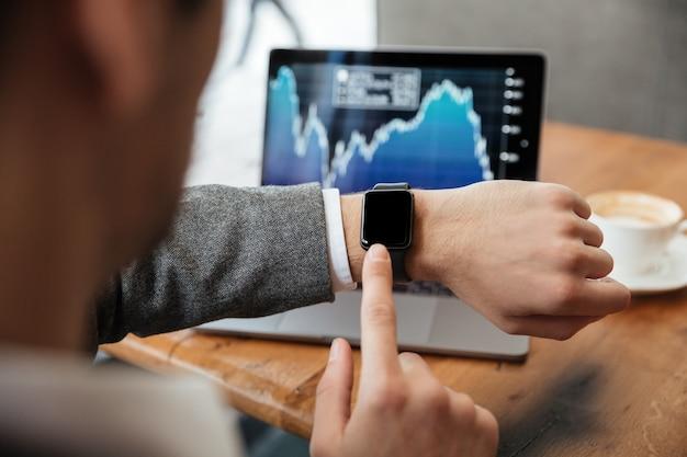 Bebouwd beeld van zakenmanzitting door de lijst in koffie en het analyseren van indicatoren op laptop computer terwijl het gebruiken van polshorloge