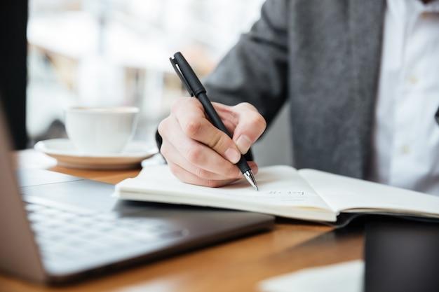 Bebouwd beeld van zakenmanzitting door de lijst in koffie met laptop computer en het schrijven van iets