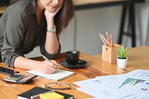 Bebouwd geschoten wijfje die op notitieboekje en financiëngegevens op lijst schrijven.