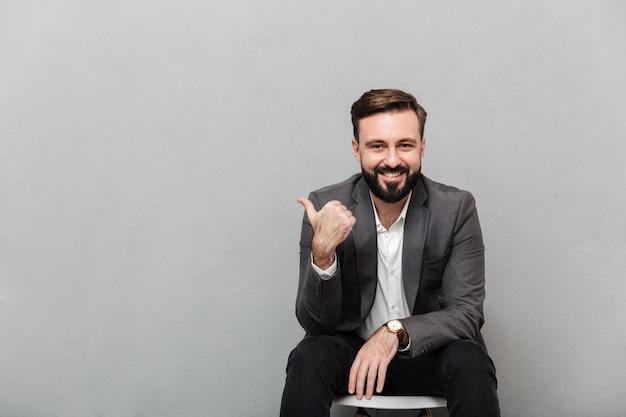 Bebouwd portret van de blije mens die op stoel in bureau rusten en duim weg gesturing, die over grijs wordt geïsoleerd