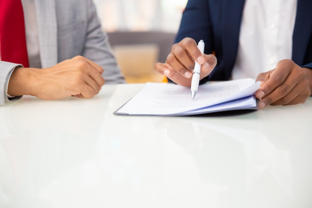 Bebouwd schot van bedrijfsmensen die contract lezen