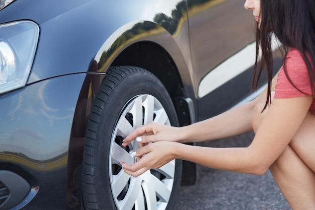 Bebouwd schot van donkerbruine vrouwelijke bestuurder die lekke autoband gaan veranderen