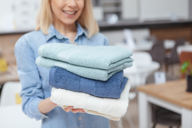 Bebouwd schot van een gelukkige vrouw die nieuwe handdoeken kopen bij meubilairopslag