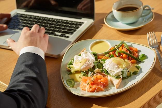 Bebouwd schot van een zakenman die aan laptop tijdens ontbijt bij koffie werkt