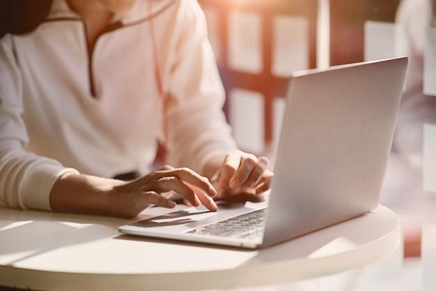 Bebouwd schot van het vrouwelijke hand typen op haar laptop thuis studiowerkplaats