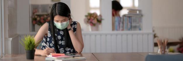 Bebouwd schot van jong vrouwelijk dragend masker terwijl het concentreren op haar opdracht in bibliotheek