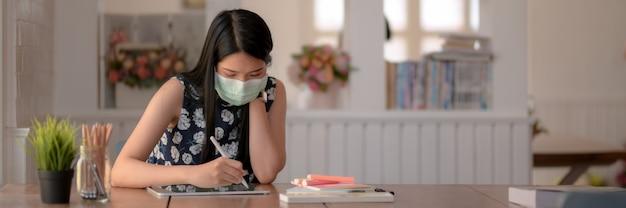 Bebouwd schot van jong vrouwelijk dragend masker terwijl het doen van haar opdracht in bibliotheek