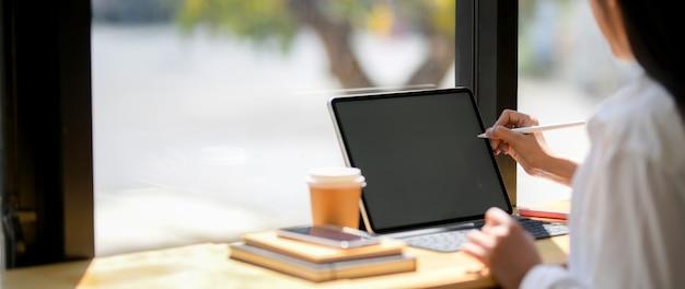 Bebouwd schot van jonge vrouwelijke student die zich op haar opdracht met tablet, koffiekop en kantoorbehoeften concentreren