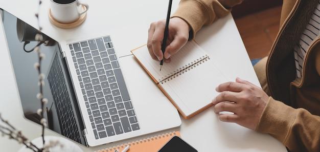 Bebouwd schot van mannelijke freelancer die aan zijn project werkt terwijl het schrijven van zijn ideeën op notitieboekje