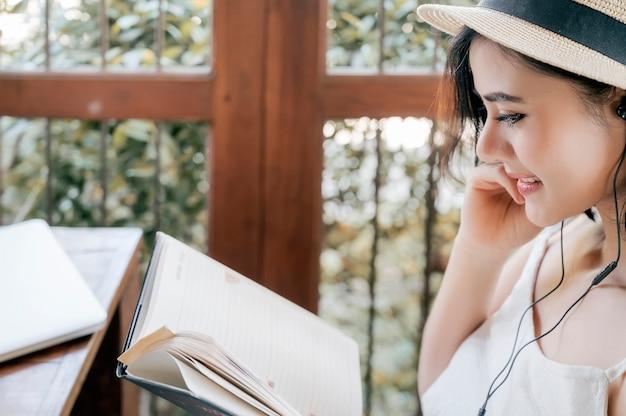 Bebouwd schot van mooie vrouw het luisteren muziek en het lezen van een boek met geluk.