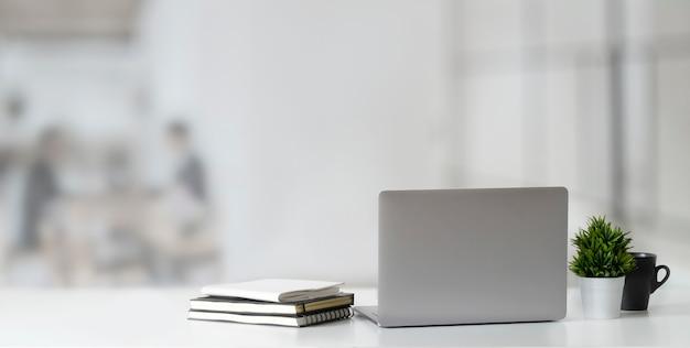 Bebouwd schot van open laptop computer op houten lijst en exemplaarruimte met vaag bureau