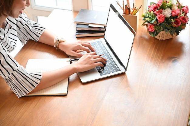 Bebouwd schot van secretaresse die modellaptop op houten lijst met hoogste mening gebruiken.