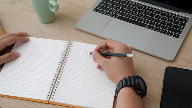 Bebouwd schot van universitaire student neemt korte nota over notitieboekje terwijl het lezen van tekst op laptop
