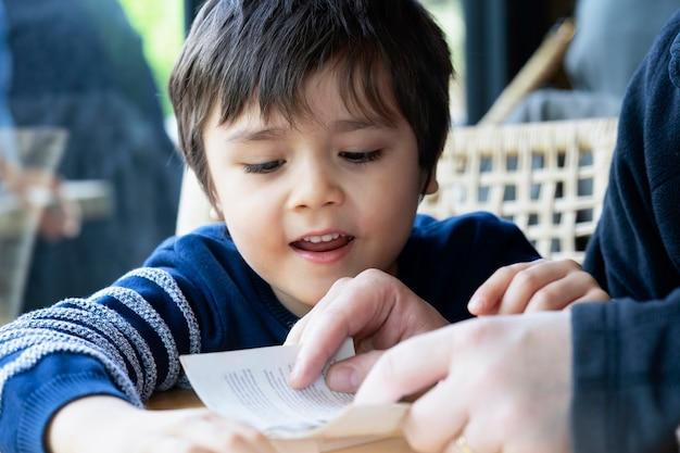 Bebouwd schot van vader die een boek leest aan zijn zoon