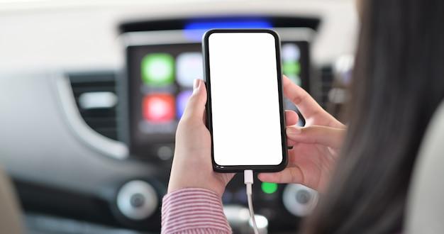 Bebouwd schot van vrouw die mobiele telefoon binnen de auto met behulp van