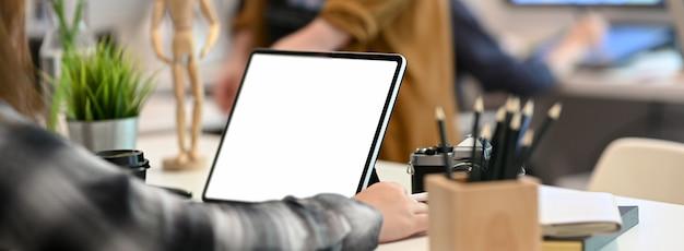 Bebouwd schot van vrouwelijke grafische ontwerper die aan tablet met lijst werken
