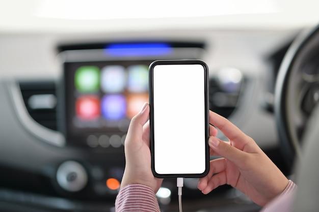 Bebouwd schot van vrouwelijke hand die mobiele telefoon in auto houdt.