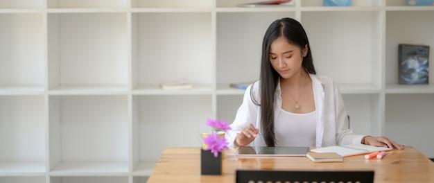 Bebouwd schot van vrouwelijke universitaire student die op tablet kijken terwijl het nemen van korte nota