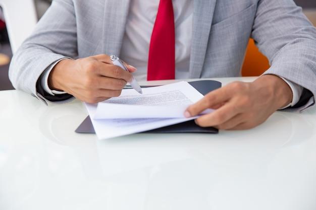 Bebouwd schot van zakenman die contract ondertekenen