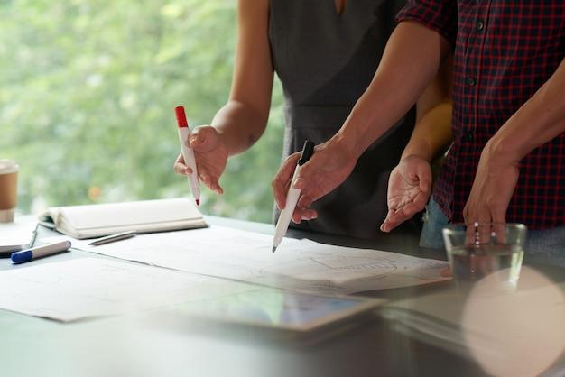 Bebouwd team dat bedrijfsgegevens bespreekt met markeerstiften