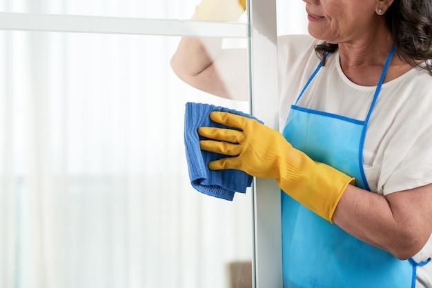Bebouwd vrouwen schoonmakend venster die speciale schort dragen