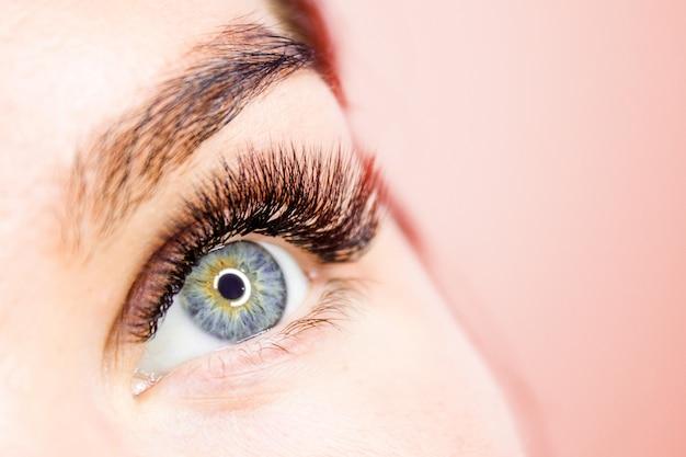 Bebouwd vrouwengezicht met oog lange valse wimpers dicht omhoog