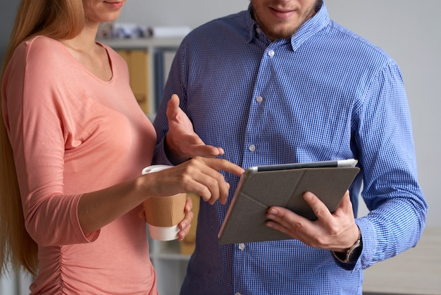 Bebouwde collega's die online nieuws bespreken op de tablet-pc