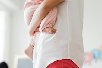 Bebouwde foto van een ouder die een baby draagt