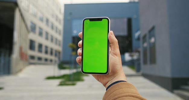 Bebouwde geschotene mening die van mannelijke hand slimme telefoon op de achtergrond van de stadsstraat met het lege exemplaar ruimtescherm houden voor uw tekstbericht of informatie-inhoud