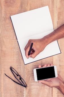 Bebouwde hand van zakenman die in notitieboekje schrijven terwijl het houden van smartphone bij bureau in bureau
