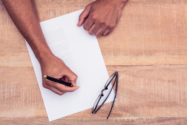 Bebouwde hand van zakenman die op papier bij bureau in bureau schrijven